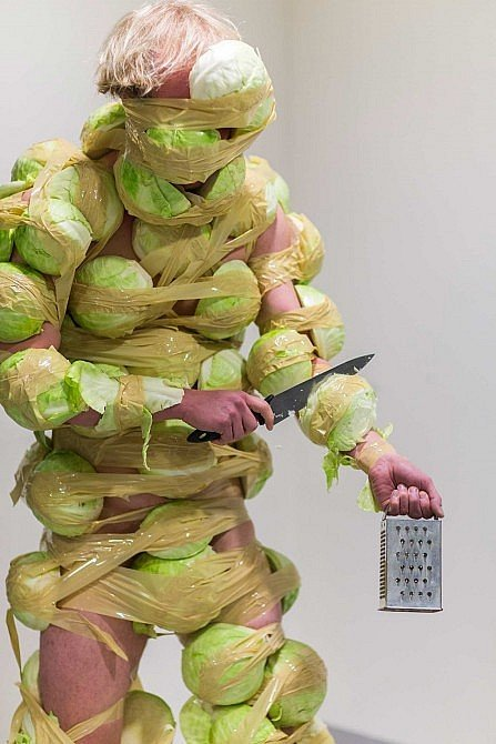 Performance artist clad in cut raw vegetables, holding a knife to their arm.
